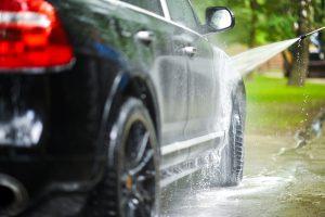 Umývanie nového auta čiernej farby vodou